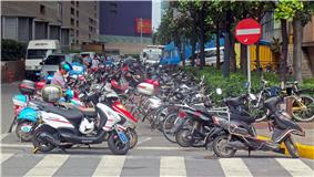 Two rows of motorbikes, many showing their age and use, parked next to a city street corner. There is a large white-bar-on-red-circle