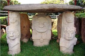 Several stone figures carrying a large flat stone on their heads.