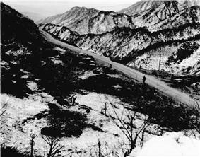 Two soldiers standing along a road that is located in a valley