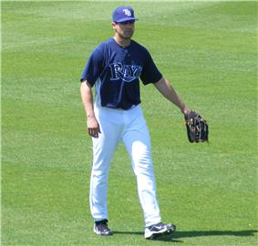 A man standing on a grassy surface wearing a baseball uniform with a dark blue shirt and white pants
