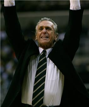 A man raising his hands in the air during a basketball game. He is wearing an open jacket with a white shirt and striped tie.