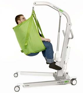 A patient sits in a sling lift with an aluminium frame