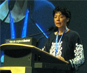 Woman with short dark hair, blue lanyard, and black and white blouse speaking at a podium