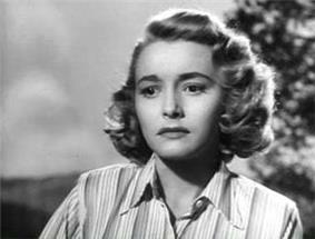 A black-and-white picture of Patricia Neal in a striped collared shirt