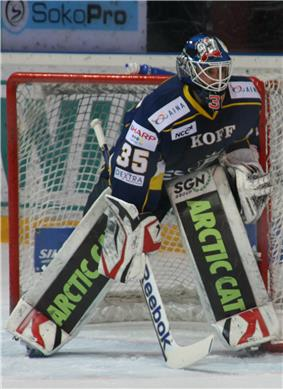 An ice hockey player standing partially crouched in goals. He is wearing a helmet, gloves and leg pads and a blue and yellow uniform.