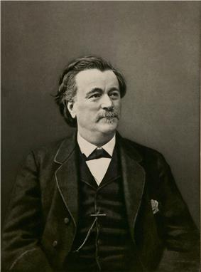 Photograph of a man, with receding hairline and grey moustache. He is dressed in a formal jacket and waistcoat, typical of Victorian fashion.