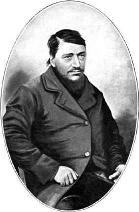 A confident-looking man of about 40 with a large dark beard. The thumb on his left hand is conspicuously absent.