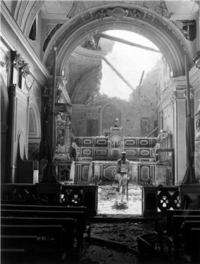 Pvt. Paul Oglesby, of the U.S. 30th Infantry, standing in reverence before an altar in a damaged Catholic Church in Acerno