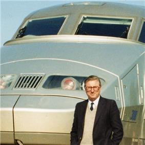 Cropped colour photograph of man in dark jacket, shirt and tie standing in front of French TGV high-speed train.