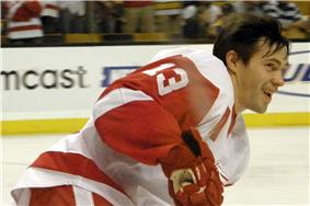 A side shot of an ice hockey player. He has medium length brown hair and is wearing a red and white uniform.