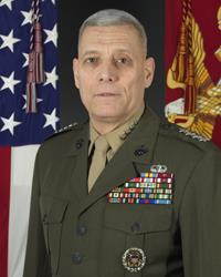 A color image of John Paxton, a white male in his Marine Corps Service A uniform. He is not wearing a hat, ribbons are visible as well as a basic parachutist badge. The Marine Corps flag and United States flag are visible in the background.