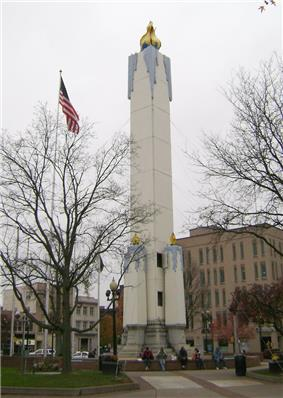A tall white structure resembling a candle with a yellow fiberglass flame on the top sits in the center of a town square-like area. At the base of the structure are two smaller, identical-looking candle-life structures. A line of people sit on a small brick wall running in front of the structure. In the background are small buildings and a flagpole with an American flag. In the foreground are two trees without leaves.