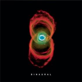 In a black background is the image of a nebula, which resembles two orange rings of smoke, with an eye-like structure in their intersection. Below it is the title