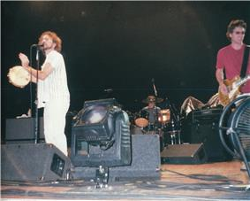 Pearl Jam on stage. Eddie Vedder sings while playing a tambourine next to a spotlight, Mike McCready plays a guitar, and Matt Cameron on the drums is seen in the background.