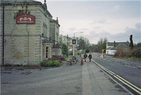 Gray stone building on the left with a pub sign outside it. A road is central to the picture with a white coloured building on the right.