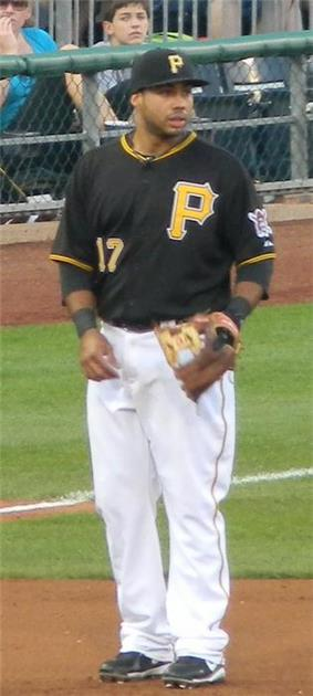 A man in a black baseball uniform and cap with yellow