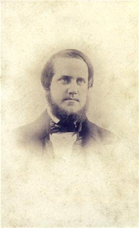 A head and shoulders daguerreotype portrait of a young man with short beard wearing a dark suit and cravat