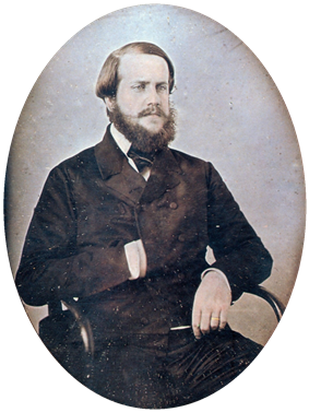 Photographic half-length portrait of a seated bearded man dressed in a dark, double-breasted coat with his right hand tucked inside the front
