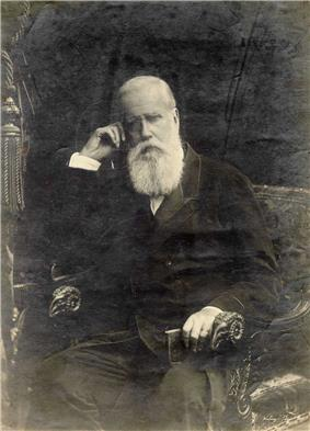 Photographic portrait of a man with a white beard seated in an armchair and holding a small book in his left hand while supporting his head with his right hand