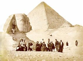 A large group of men and women are gathered below the head of the Sphinx with the Great Pyramid looming behind