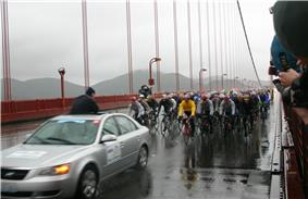 A group of bicyclist following a car.