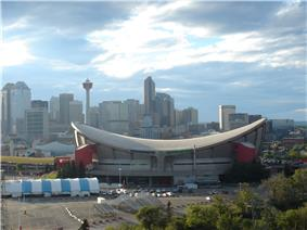 Exterior shot of an indoor arena.  The building has a sloped roof in the shape of a reverse hyperbolic paraboloid and a primarily-concrete outer facing with red towers at the corners.  Several skyscrapers are visible in the background.