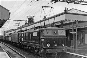 Black-and-white photo of electric locomotive with overhead wiring at a station