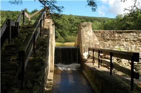 Water pours over a narrow spillway with a sunlit stone dam structure on either side