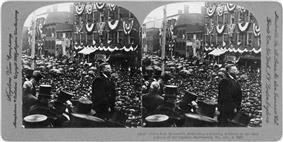 Two identical photos of a man looking out over a large crowd. The images are mounted side-by-side on a card.