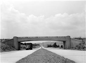 Four-lane highway with overpass, photographed from median