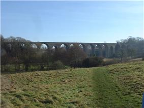 stone viaduct with multiple arches, partly obscured by tress