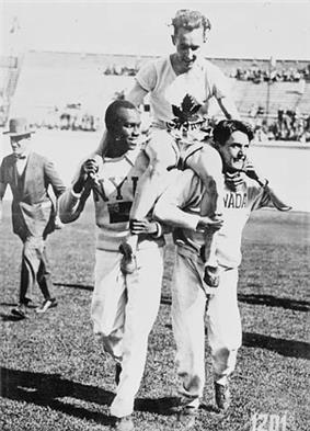 A man is carried on the shoulders of two other men. He is in a white shirt and shorts with a stylized maple leaf logo above the letters