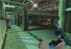 A metallic room with columns and computers located in the farthest side. A hand holding and reloading a gun is seen on the bottom right corner. A crosshair and graphics symbols representing ammunition are also visible.