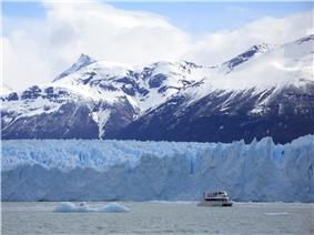 A tourist yatch near a glacier wall