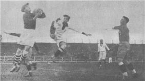 An action shot from a football match. A goalkeeper jumps and catches the ball.