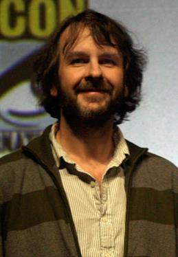 A picture of a bearded man with long black hair. He wears a beige and white striped shirt underneath a charcoal striped jacket.