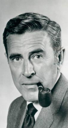 A man with dark hair, wearing a suit, including a tie also having a pipe in his mouth.