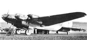 Three-quarters view of a large four-engined parked aircraft with a conventional undercarriage with a group of people clustered in the left foreground and another on the other side of the fuselage in the background