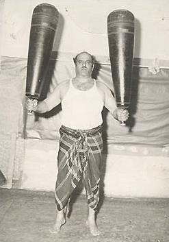 The pahlevan Mustafa Tousi holding a pair of meels