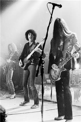 A black-and-white photo of the band performing onstage