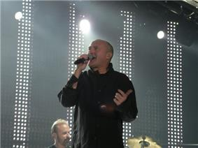 A man with a shaved head wearing black and singing into a microphone. The background contains dotted lighting on a stage.
