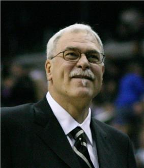 A man with white hair, wearing a black suit, white shirt and tie, at a basketball game.