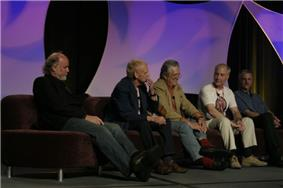 Five older men sit on a couch, with an arched, decorative purple background behind them. Ralston, leaning back in his seat, has short hair and wears a shirt with slacks.
