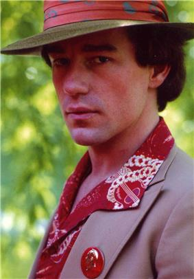A portrait photo of Hartman looking side-ways on at the camera with a serious expression on his face. He has a red rimmed hat on, a brown jacket, a gold and red shirt and a button was a man's face on it.