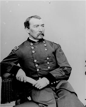 Man with moustache sitting down with arm on table in uniform with two columns of buttons