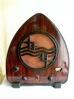 Curved, triangular radio with brown wooden cabinet