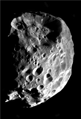 An approximately spherical heavily cratered body is illuminated from the bottom-right. The terminator runs near the left and top limbs. There is huge crater at the top, which affects the shape, and another slightly smaller at the bottom.