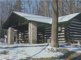A snow-covered log cabin with a porch supported by stone pillars