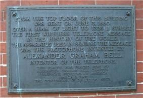 An image of darkened brass historical plaque with a streak of green corrosion running down it, mounted on the exterior side of a brick building.