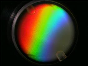 Photo of a circular dish containing a rainbow like pattern.